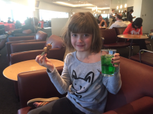 Maddie drinking all of the apple green Fanta the Japan Sky Lounge could provide